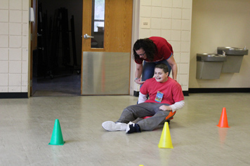 A special education student in a red shirt smiles as his teacher pushes him through an obstacle course