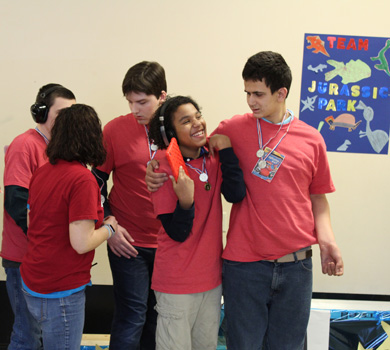 A group of students in an autism support program smile as they work on a project together.