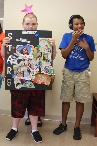A student in an autism support program shows off his school project while a friend smiles beside him.