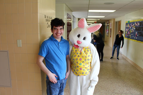 A special education student in a blue shirt poses and smiles with the Easter bunny.