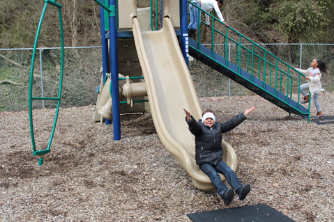 Students in an autism support program smile from the playground of their special education school