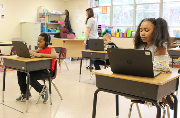 Students in a special education look down at laptops as they complete their coursework