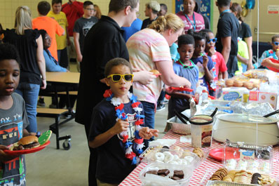 A young boy wears sunglasses and a flowered necklace while others gather food during an event at a special needs school
