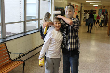 Two young boys show off their costumes in the hallway as their special education school prepares for Halloween