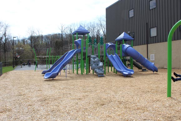 A blue slide and playground equipment stand ready outside a special needs school