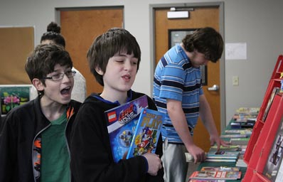 Two boys in an autism support educational program review books at a table in their school