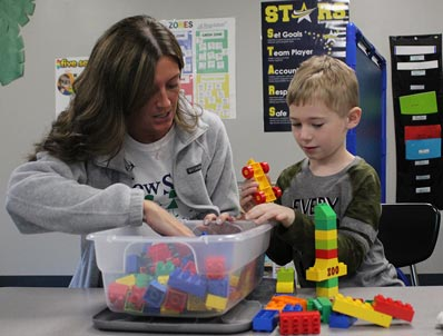 A special education student works on a project with his instructor.
