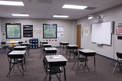 Empty desks face a smart board in an emotional support classroom at a special needs school