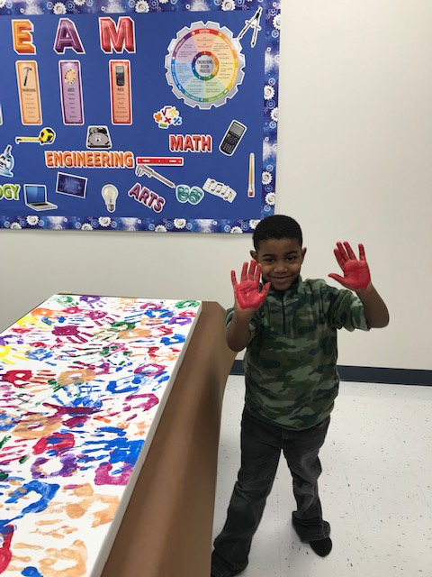 A special education student shows off his paint-covered hand near an art project