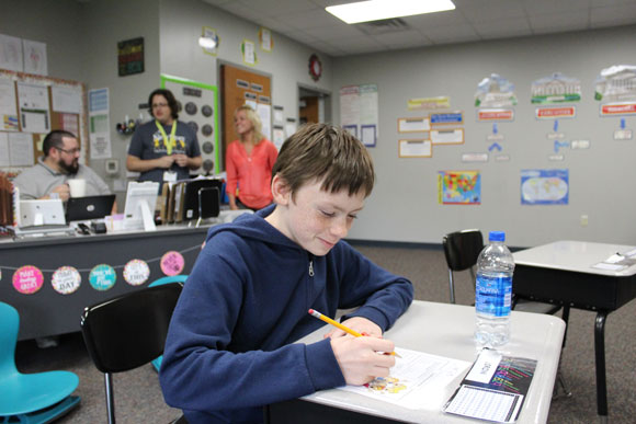 An elementary school special education student works on an assignment at his desk