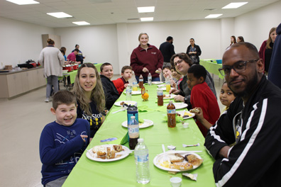 Special education students, staff, and families smile at a buffet.