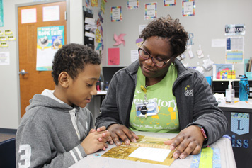 A special education teacher works with an elementary school boy on his assignment