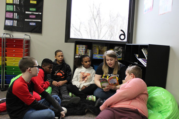 A group of emotional support students gather around their special education teacher in the school library.