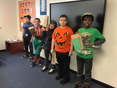 Five students in an emotional support classroom smile in Halloween themed clothes.
