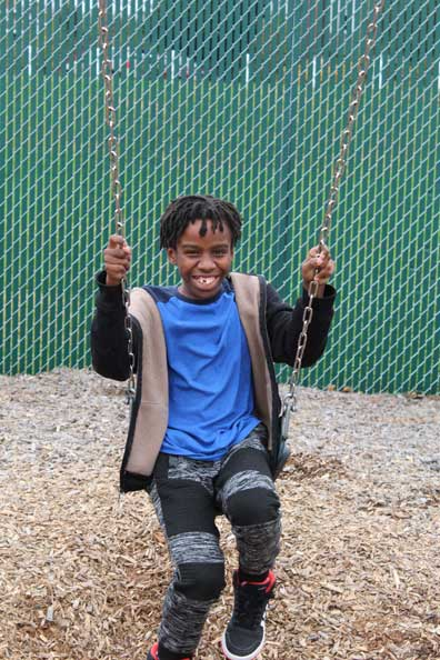 A special education student smiles from the swing on his school's playground