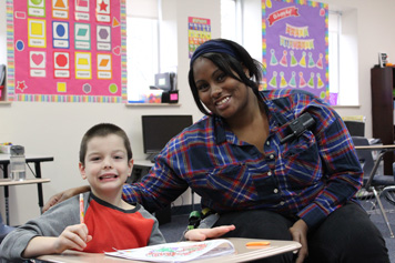 An elementary school boy in an emotional support program smiles with his special education teacher