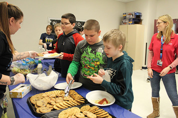 Special education students gather cookies from a table at their school.