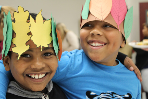 Two elementary school boys smile while wearing fall themed hats in their special education school.