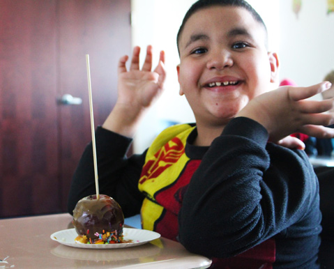 A young boy smiles over his caramel apple at his special education school.