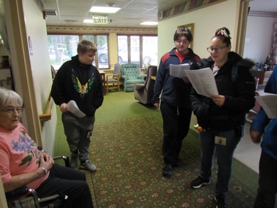 Members of an emotional support class visit with residents of an assisted living home during a field trip