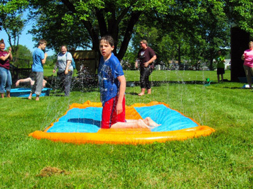 A young boy in a blue shirt looks at the camera from the center of a sprinkler pad