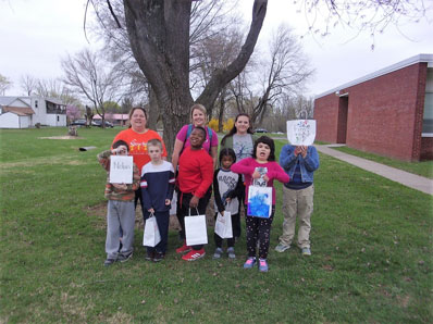 An elementary autism support class shows off bags by a tree outside of their special education school.