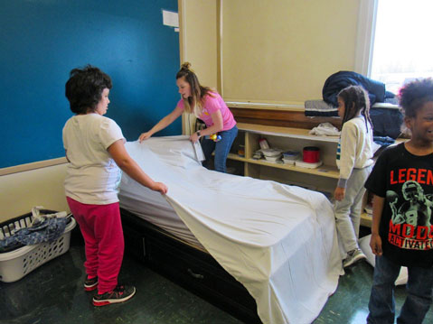 Three students in an autism support program work with their special education teacher on making a bed