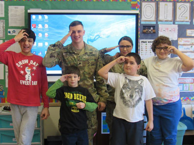 Four boys from a special education class and their teacher salute with a member of the armed forces who visited.