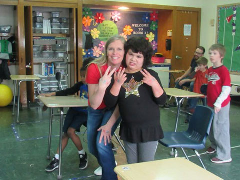 A young girl from an autism support classroom smiles with her special education teacher