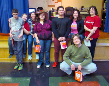 A group of special education students and teachers smile while holding Valentine bags.