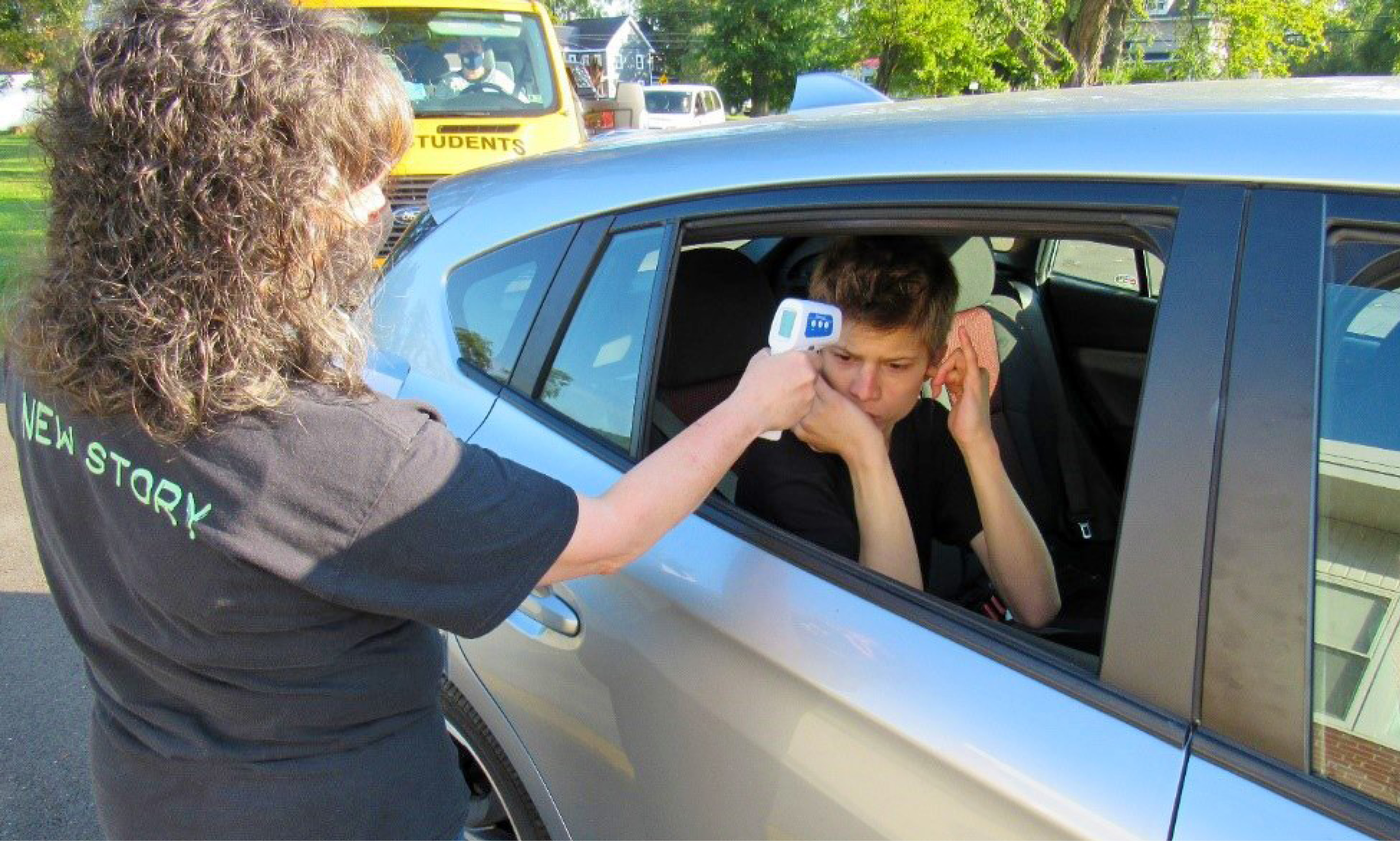 Special education staff performs a temperature check on a special education student sitting in a car.