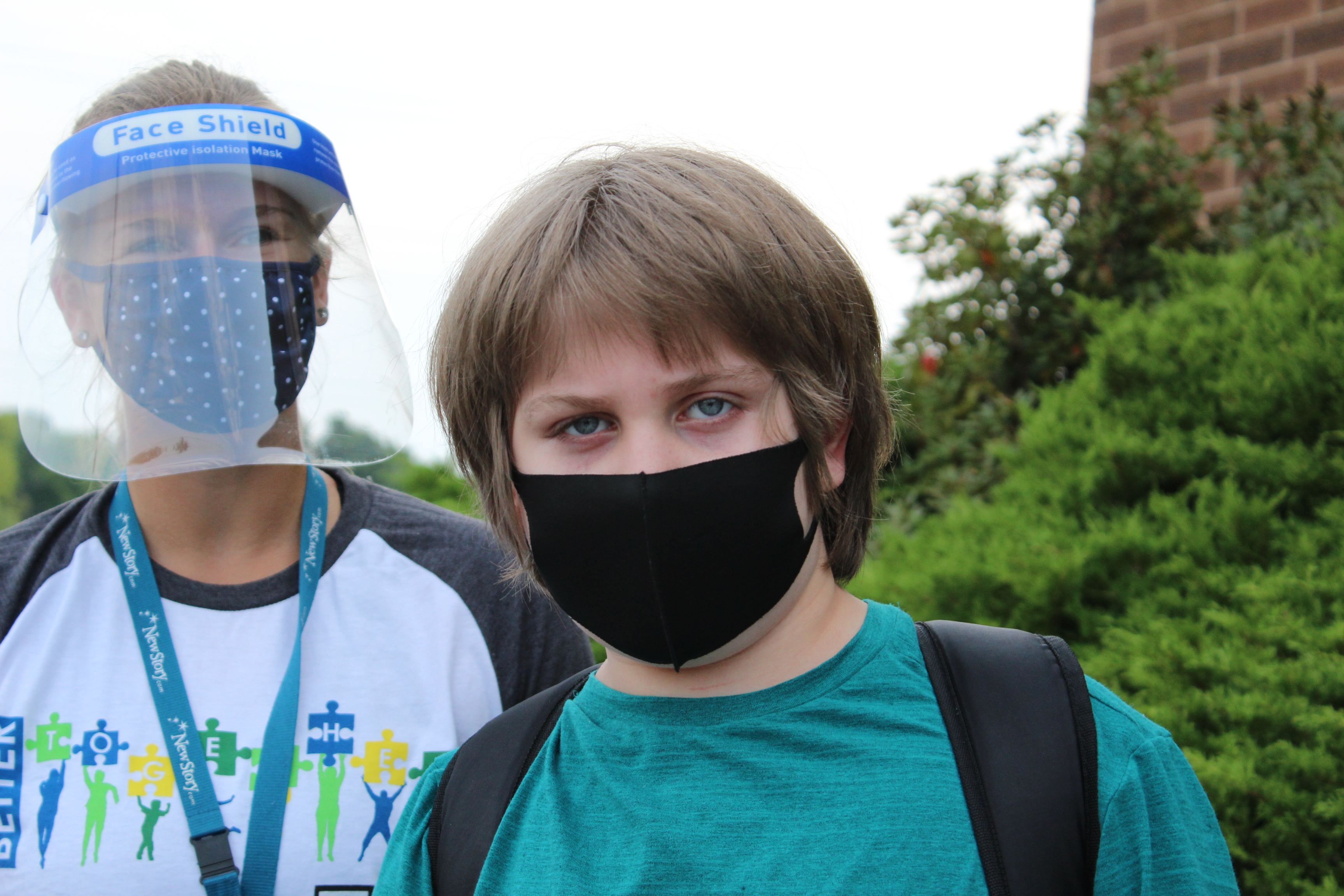 Special Education Student in mask outside, Teacher with face guard and mask.