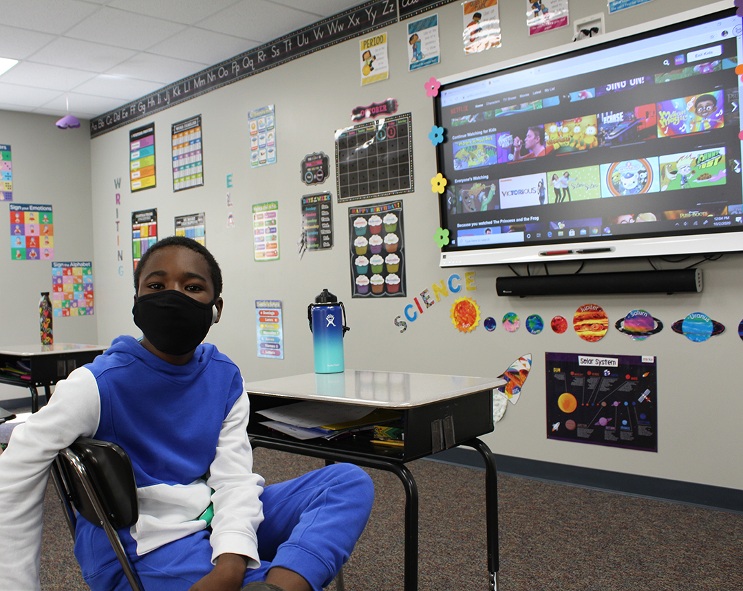 Special Education Student with mask sits at his front row desk in front of his classroom's smartboard, which is showing various kid's videos for break time music.