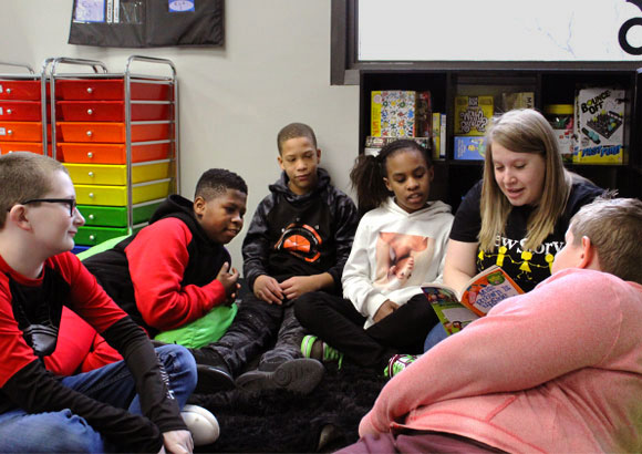 A special education teacher reads to a large group of students in her classroom.